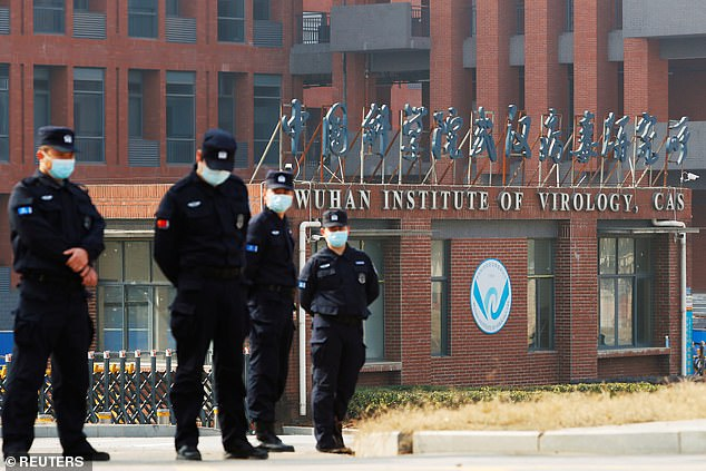 Pictured:Security personnel keep watch outside Wuhan Institute of Virology during the visit by the World Health Organization (WHO) team in February